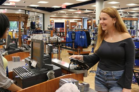 Photo of a female student using her DukeCard to make a purchase at a Duke store.
