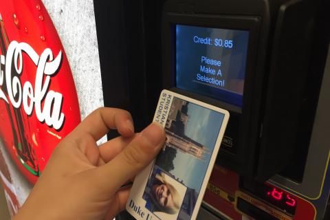 Photo of a person using a DukeCard to pay at campus vending machine