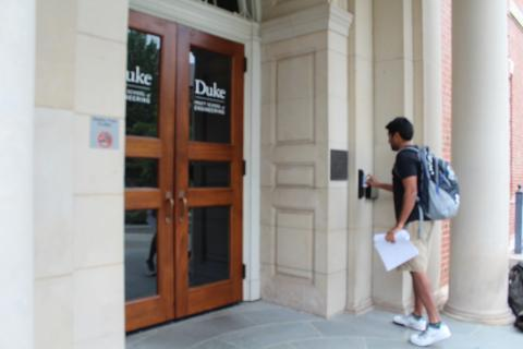 Photo of a male student entering an academic building by swiping his DukeCard.